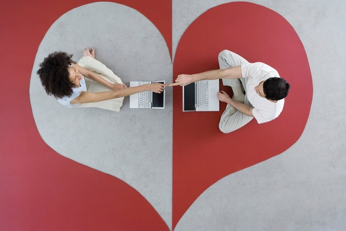 a man and a woman sitting across from each other on a heart shaped floor