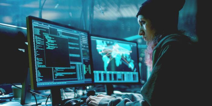 the deep web - a woman sitting in front of two computer screens