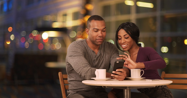 Happy Black couple in coffee shop at night.