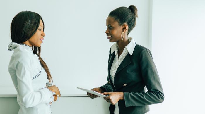 two women speaking at work
