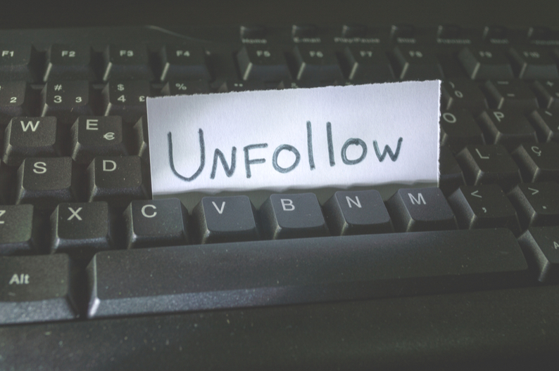 background check - a note that says unfollow between keyboards