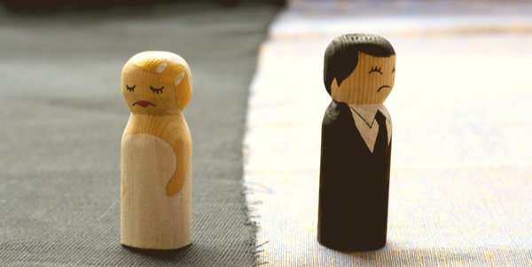 wooden figures of a bride and groom standing back to back
