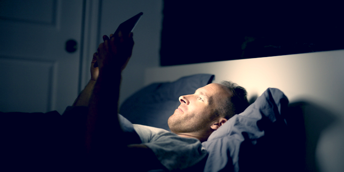 negatives of social media - a man lying in a bed and looking at a tablet