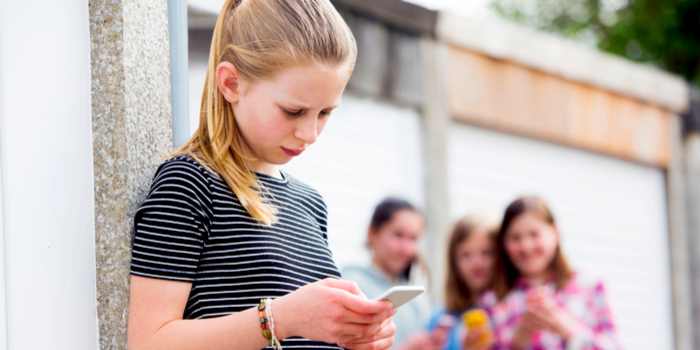 negative effects of social media - an upset girl with a phone in her hand