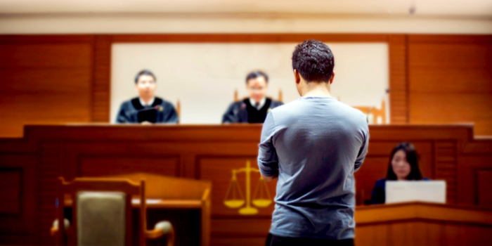 criminal sentencing statistics - a man standing in front of a judge in court