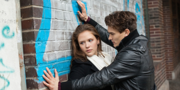 a man imposing himself against a woman leaning on a wall