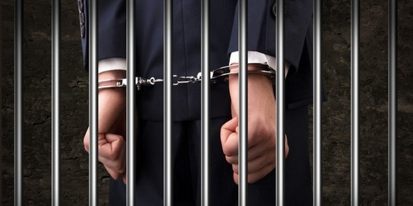 cuffed hands of a man behind bars
