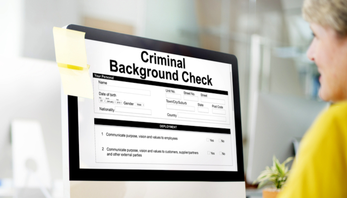 background check - a woman conducting an online criminal background check