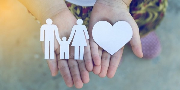 two hand holding a paper cutout of a heart and a family
