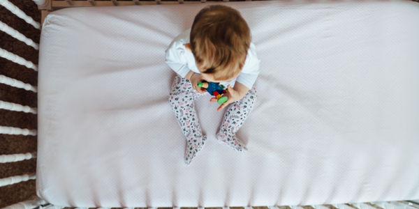 a baby in a crib photographed from above