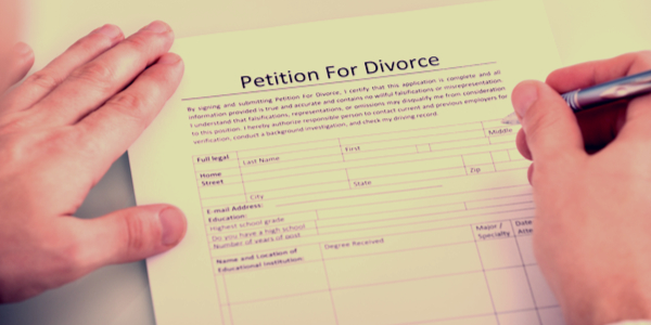 a hand signing a divorce agreement