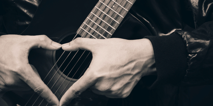 Most popular love songs - two hands forming a heart in front of a guitar