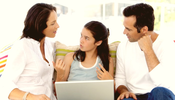 a teenager talking to her parents with a laptop on her lap