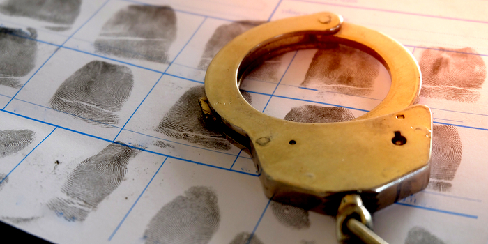 criminal background check - handcuffs on a fingerprint sheet