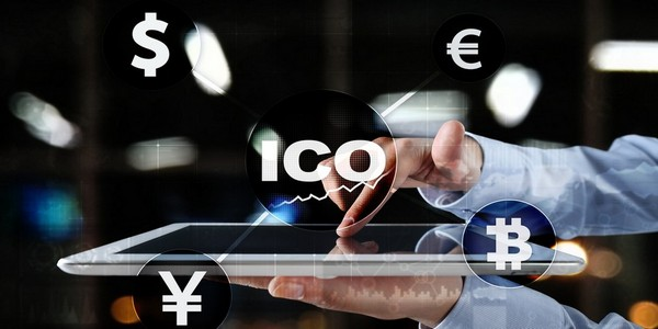 an illustration of the word ICO and currencies floating on top of a computer