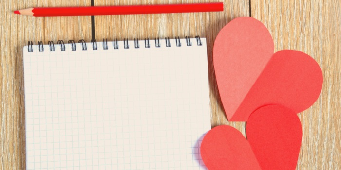a notepad with cutout hearts near it