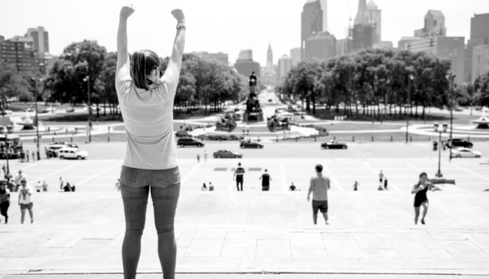 philadelphia pennsylvania - a woman holding her arms up at the top of the rocky steps