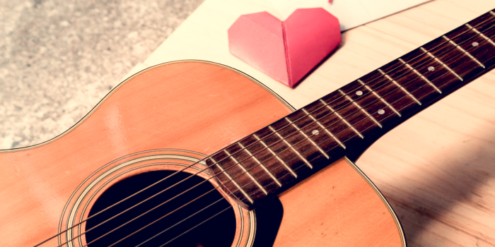 Most popular love songs - a guitar lying next to a heart shapes piece of paper